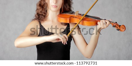 Beautiful violinist redhead woman on gray background - stock photo