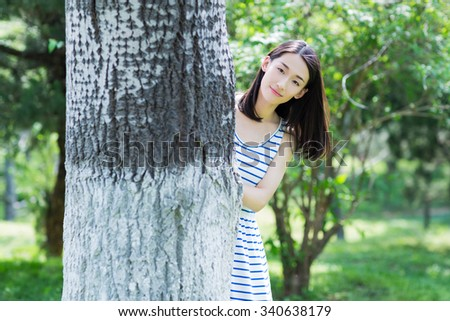 beautiful, vivacious girl, hiding behind trees, play hide and seek - stock photo