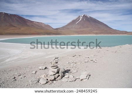 Beautiful volcano landscape with a green lagoon in  Andes of Bolivia - stock photo