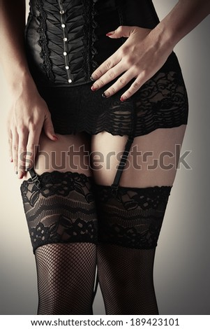 Beautiful, voluptuous and sexy caucasian adult woman in black fishnet stockings and garters in a boudoir setting lit from the side with window light. - stock photo