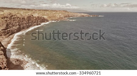 Beautiful water of the ocean and mountain background, summer beach on island Maui, Hawaii, clifs, grass and trees, rocks on the ocean shore.