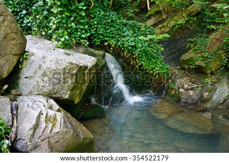 Beautiful water stream flowing between stones in the forest - stock photo
