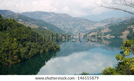 beautiful water surround by mountains in the begnas lake in pokhara at nepal - stock photo