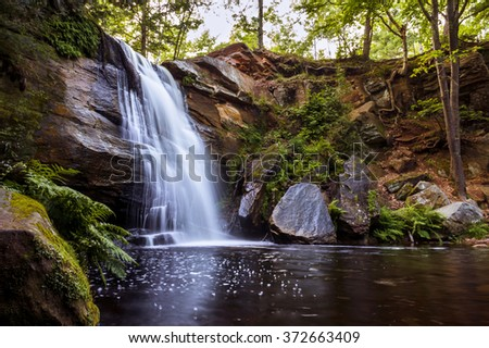 Beautiful Waterfall Cascade Flows into Peaceful Tranquil Reflecting Pool. Serene Natural Water Landscape Background. - stock photo