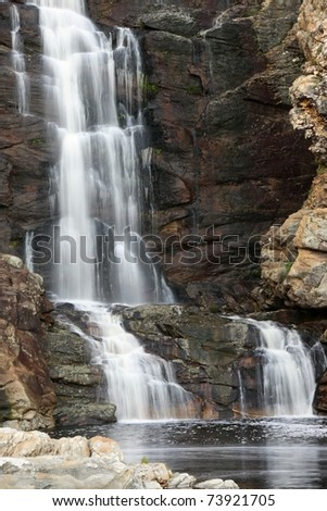 Beautiful waterfall cascading down rocks into a pool below - stock photo