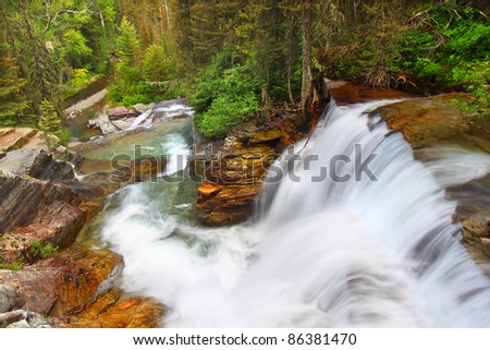 Beautiful waterfall flows through the pine forests of Glacier National Park in Montana - stock photo