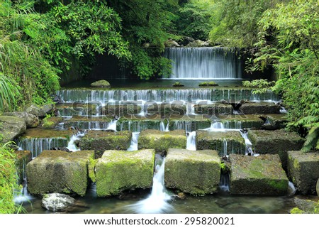 Beautiful waterfall in a shady jungle ~ Cool refreshing cascades hidden in a mysterious forest of lush greenery - stock photo