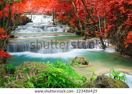 Beautiful waterfall in autumn forest  - stock photo