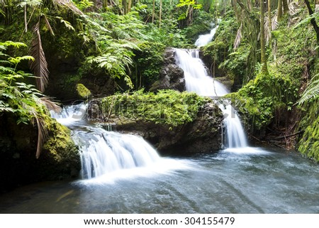 Beautiful waterfall in Hawaii fed by frequent rainfall forms cascading flows into a natural pool. - stock photo