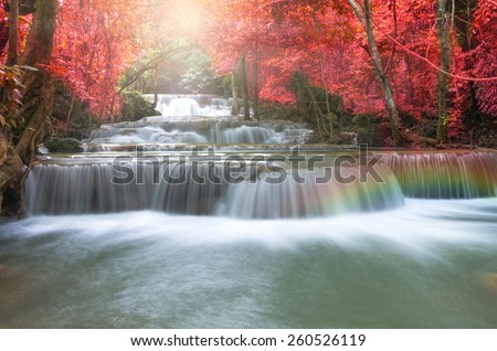 Beautiful waterfall in soft focus with rainbow in the forest - stock photo