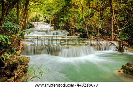 Beautiful waterfall in spring forest in Kanchanaburi province, Thailand.