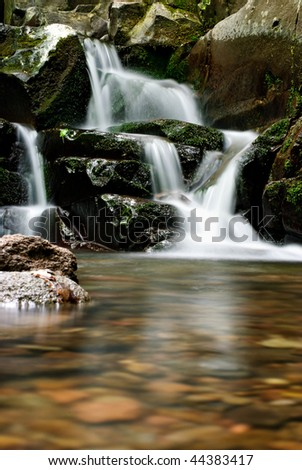Beautiful waterfall in the forest at autumn - stock photo