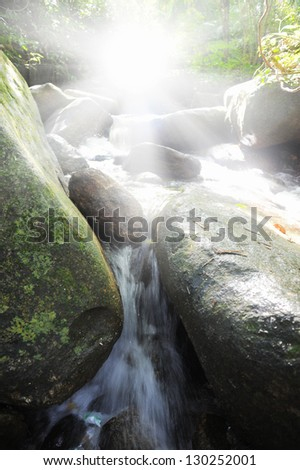 Beautiful waterfall in the forest on a sunny day - stock photo