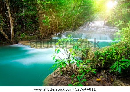 Beautiful waterfall in tropical forest with sunlight - stock photo