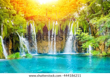 Beautiful waterfall landscape. Green forest with sun light, pond and water stream. - stock photo