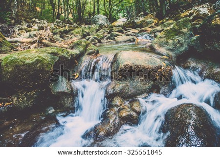 Beautiful waterfall on a mountain slope. Fast river with cascades. - stock photo