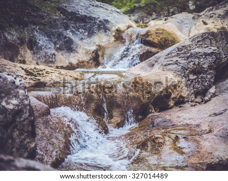 Beautiful waterfall on a mountain slope. Fast river with cascades.