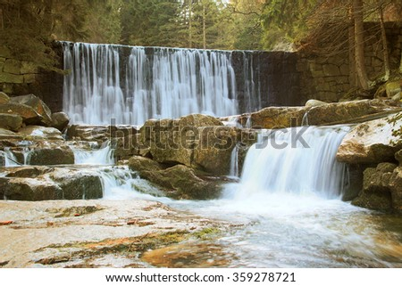 Beautiful waterfall on a mountain slope. River with cascades.