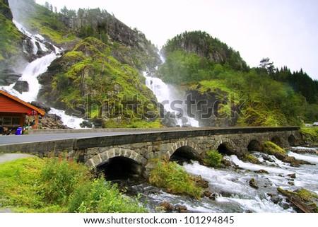 Beautiful waterfall scenery with old bridge - stock photo