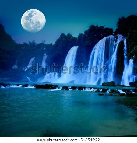 Beautiful waterfall under moonlight at night time - stock photo