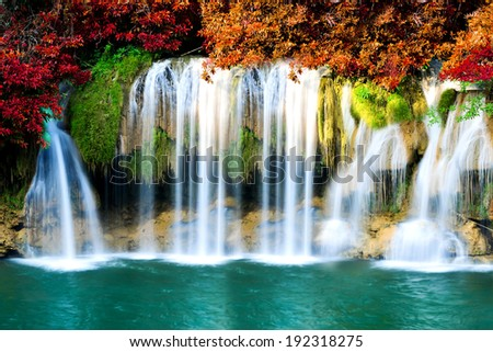Beautiful waterfall with autumn forest - stock photo