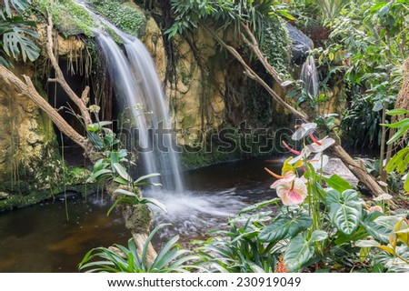 Beautiful waterfall with flamingo flowers in tropical garden - stock photo