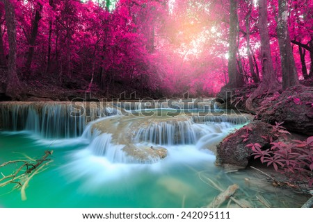 Beautiful waterfall with sunlight rays in deep forest, Erawan National Park in Kanchanaburi, Thailand - stock photo