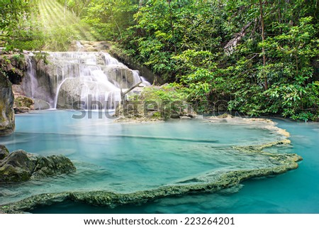 Beautiful waterfall with sunshine in deep forest, Erawan waterfall, Thailand