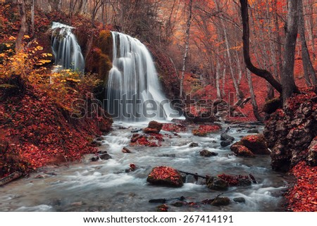 Beautiful waterfall with trees, red leaves, rocks and stones in autumn forest. Silver Stream Waterfall (Autumn forest in Crimea) - stock photo