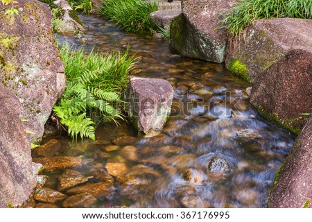Beautiful Waterfalls over a jumble of boulders in forest. - stock photo
