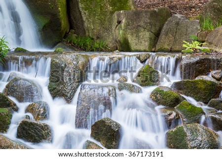 Beautiful Waterfalls over a jumble of moss-covered boulders in forest. - stock photo