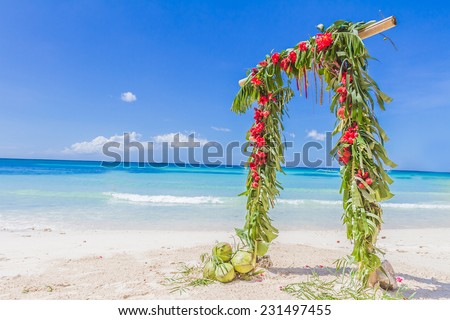 beautiful wedding arch decorated with palm trees and flowers on tropical sand beach, beach wedding setup - stock photo