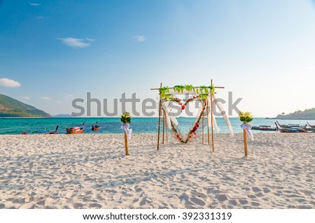 Beautiful wedding arch floral decorations on the beach - stock photo