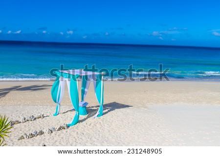 beautiful wedding arch on tropical sand beach, outdoor beach wedding set up - stock photo