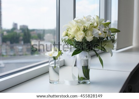 Beautiful wedding bouquet in a glass vase. Flowers on white windowsill. Boutonniere in a small vase. The window in the background. - stock photo