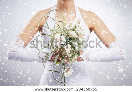 Beautiful wedding bouquet in bride's hands. Winter background with a snowflakes. - stock photo