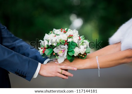 Beautiful wedding bouquet in brides and grooms hands - stock photo