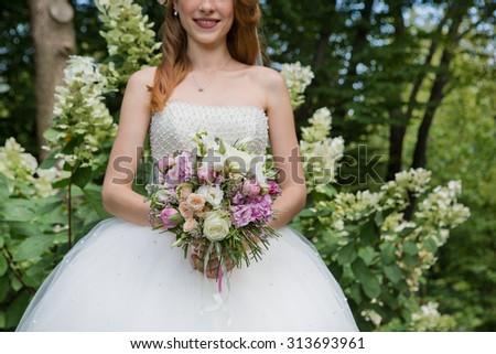 beautiful wedding bouquet in hands of bride - stock photo