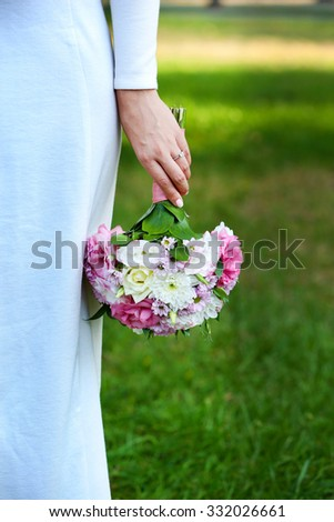 Beautiful wedding bouquet in hands of bride on nature background