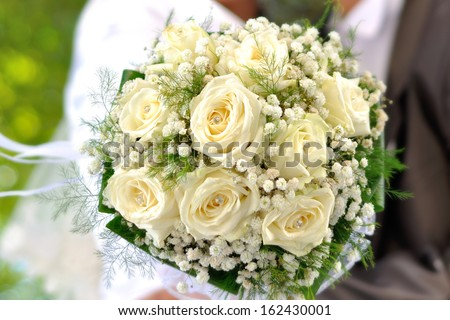 Beautiful wedding bouquet in hands of the bride and groom