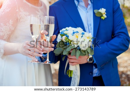 Beautiful wedding bouquet in hands of the bride and groom. Wedding rings. - stock photo