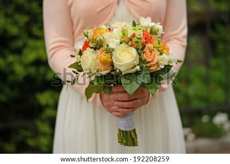 Beautiful wedding bouquet in hands of the bride in outdoor. Focus on flowers. closeup - stock photo