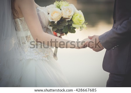 Beautiful wedding bouquet in hands of the bride is illustrated in a wedding as Asian