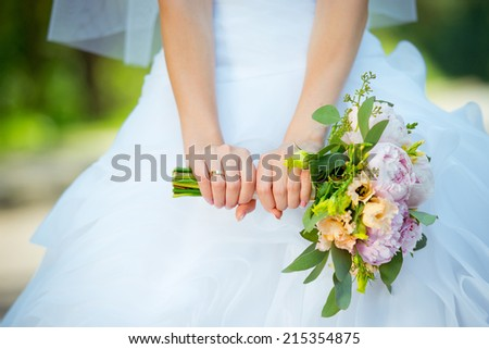 Beautiful wedding bouquet in hands of the bride. Wedding rings. - stock photo