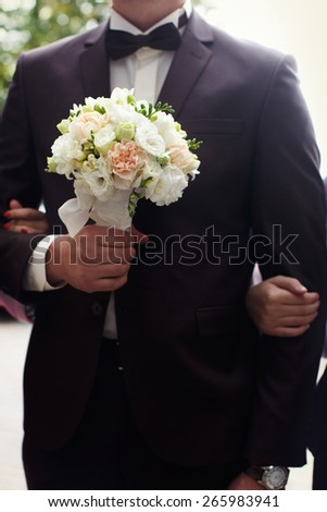 Beautiful wedding bouquet in hands of the groom. Gift to the bride. Roses, peonies taped and lace.Blue classic designer suit with a yellow tie and buttonhole. - stock photo
