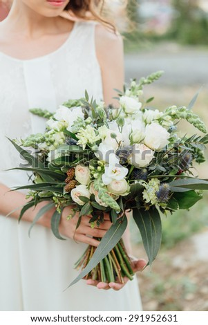 Beautiful wedding bouquet in the bride's hands  - stock photo