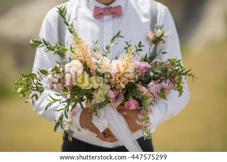 beautiful wedding bouquet in the hands of the groom