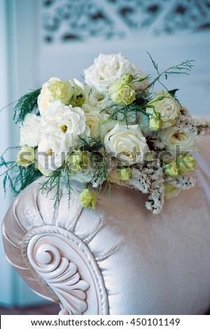 Beautiful wedding bouquet lies on vintage beige chair. Bouquet consists of white roses and eustoma. - stock photo