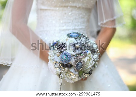 Beautiful wedding bouquet of brooches in hands of the bride - stock photo