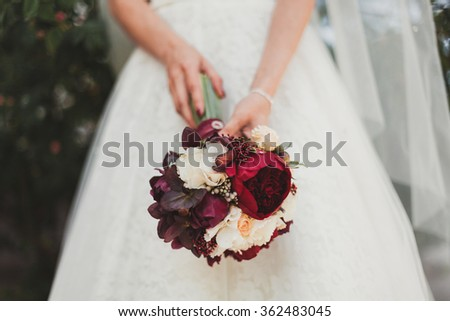 Beautiful wedding bouquet of flowers in hands of the bride